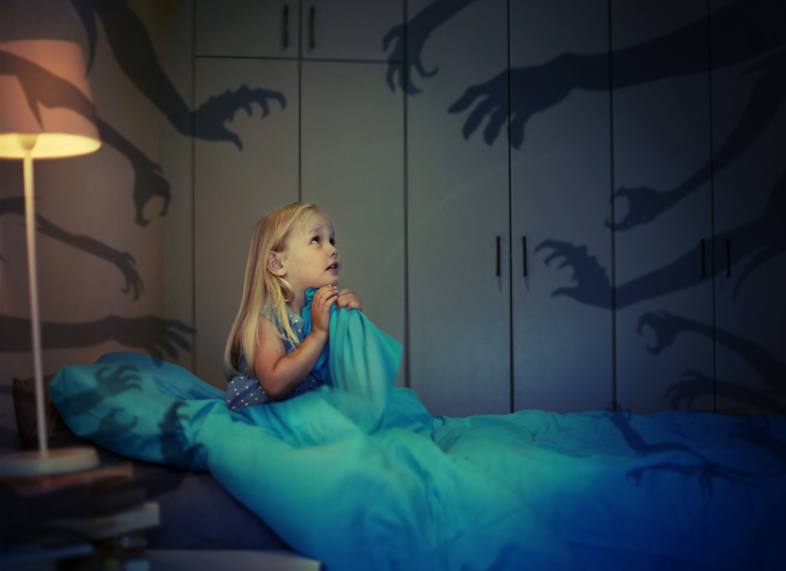 little girl in bed having a nightmare that shadow hands are reaching for her