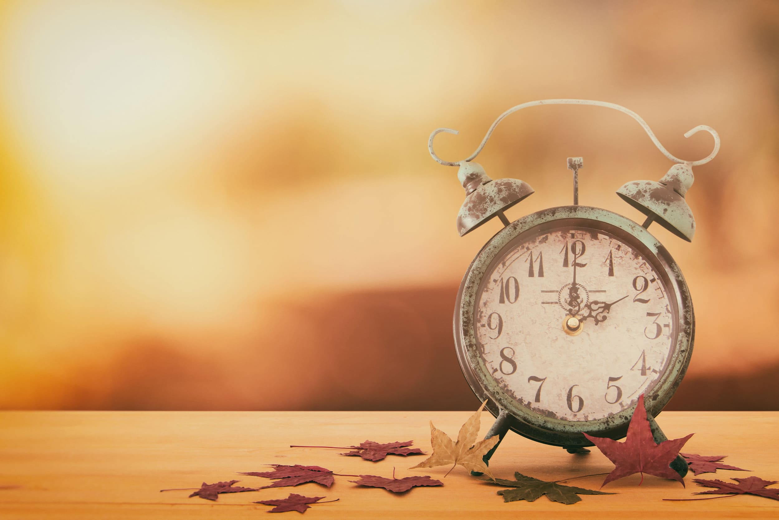 antique alarm clock on table surrounding by fall leaves with sunlight shining in the background