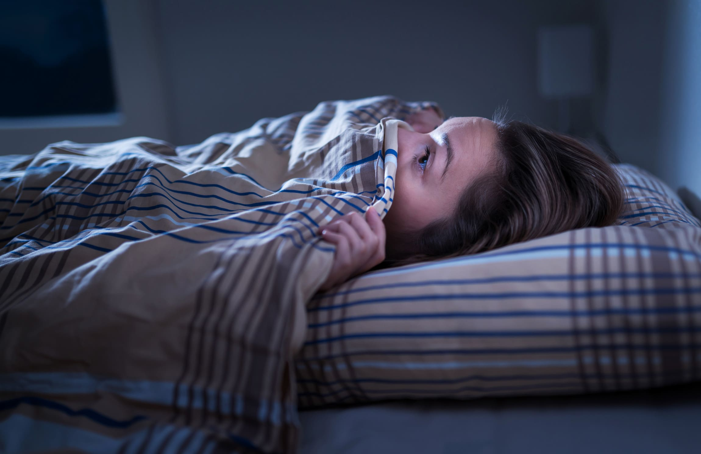 woman lying under the covers in the dark scared to come out