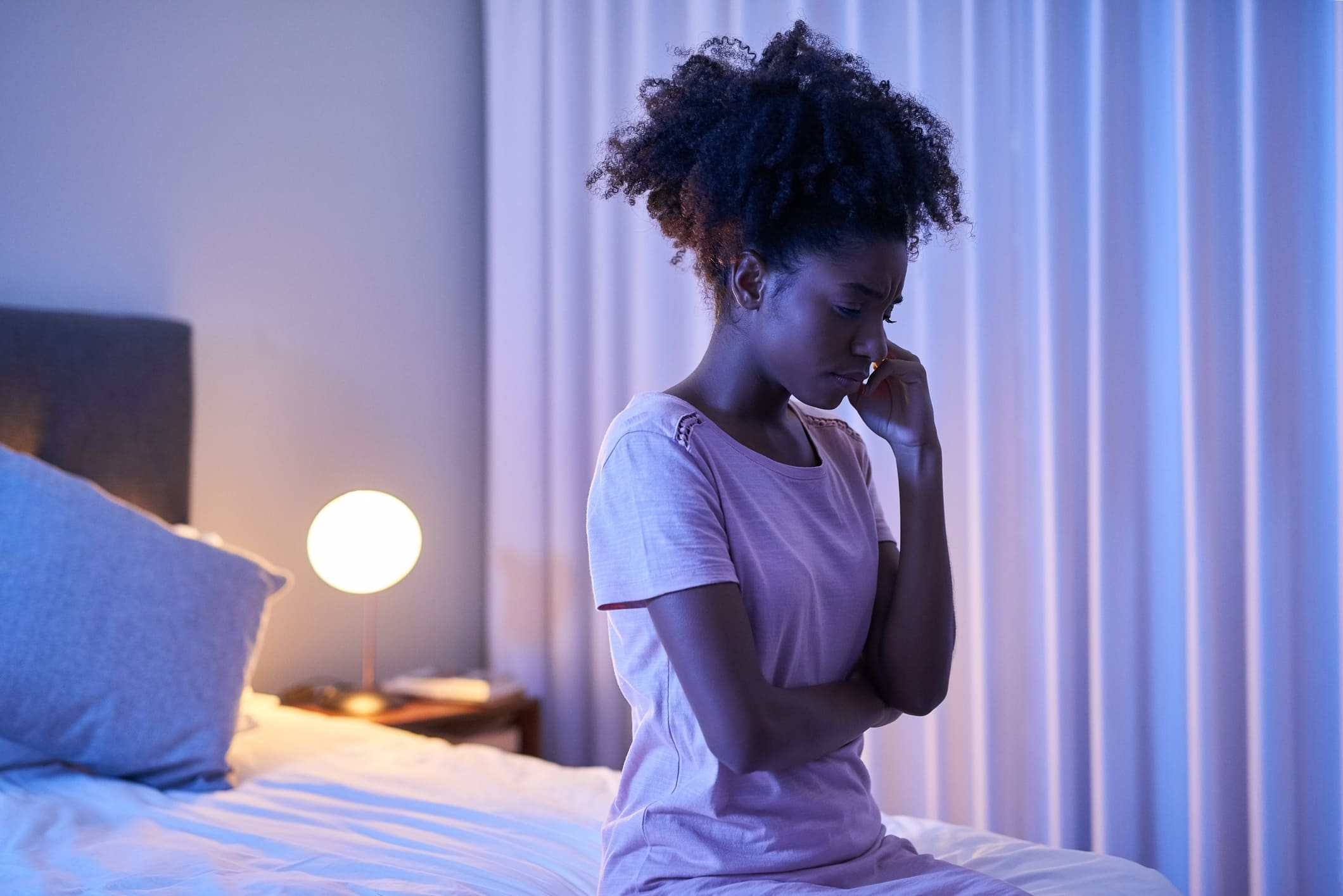 young woman sitting on edge of bed in the middle of the night with hand held to her face and frowning
