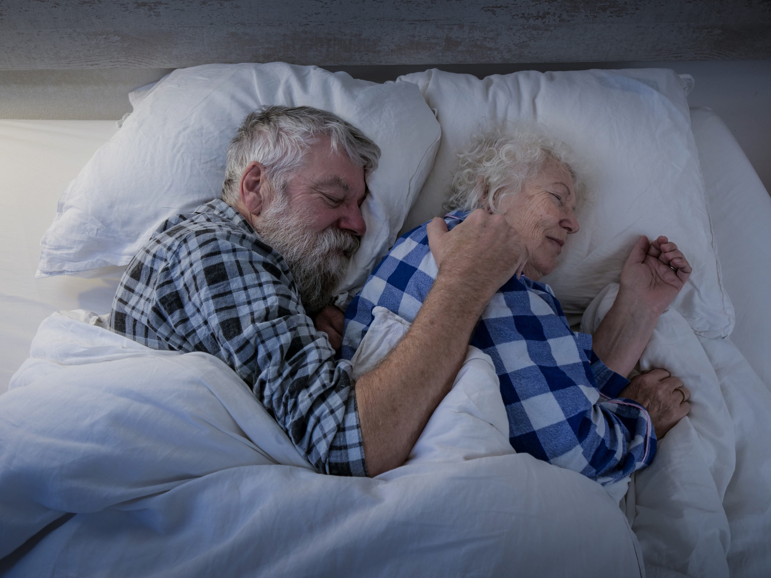 older couple sleeping together in plaid shirts on comfy bed