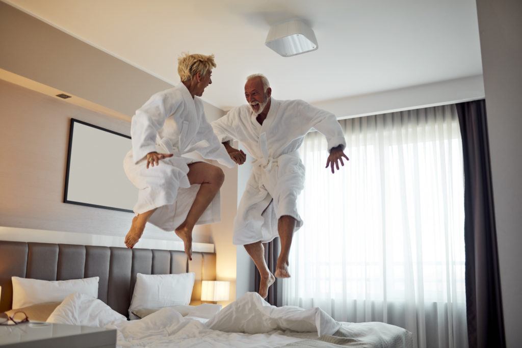 older couple in robes jumping up and down on hotel bed