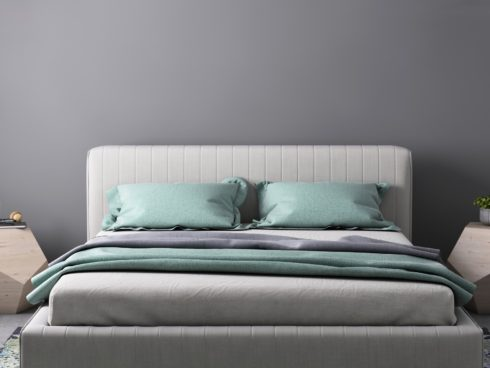 grey and teal mattress on clean creme linen bed frame with geometric night stands and lamps